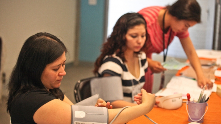 Patients take their own blood pressure while a facilitator reviews their files during a Centering Pregnancy session at San Francisco's Homeless Prenatal Program, which collaborates with San Francisco General Hospital and offers space for the meetings.