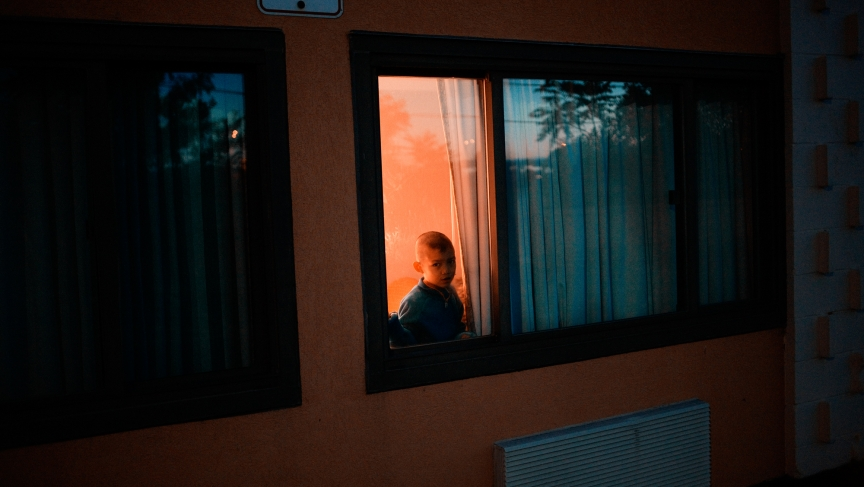 A young Burmese boy looked out from his hotel room in Los Angeles, shortly after arriving to the United States as a refugee. Photographed in June 2010.