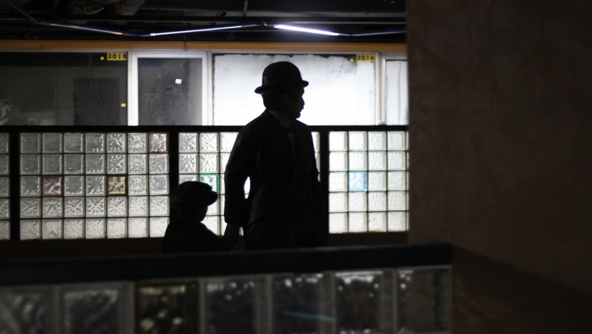A statue of Charlie Chaplin (holding the hand of a statue of what appears to be Chaplin as a child) watches over the abandoned six-theater movie theater complex in the bus station.