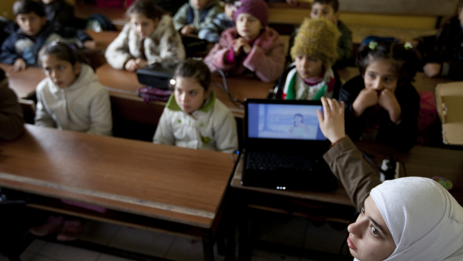 Rafah Al Tinawie sets up a DVD player to show a video-story to her students