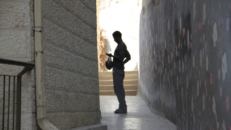 An armed Israeli security guard enters a Jewish property in Silwan.