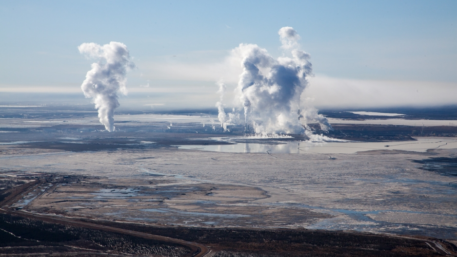 The view toward's Syncrude's Mildred Lake site, where bitumen is extracted from oil sands. A tailing pond is in the foreground, with steam and smoke rising from the upgrading facility behind it.