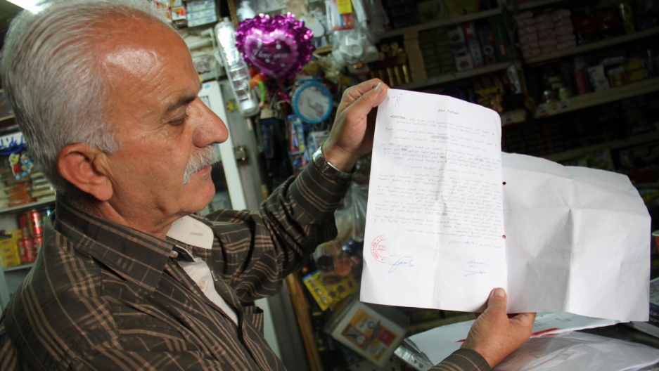 The father of Anan Baydoun holding the deed of sale showing his son sold his family's property to Farid Hajj Yihyeh, a Muslim man who residents accuse of acting as a broker for Jewish settlers.