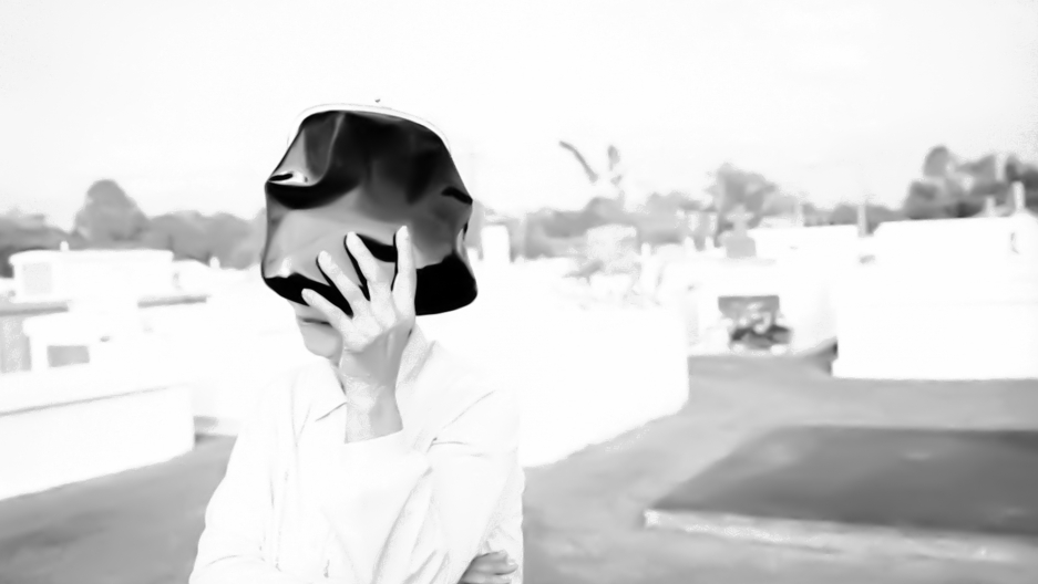Woman shielding her face in a cemetery in St. Martinsville, Louisiana, 1998