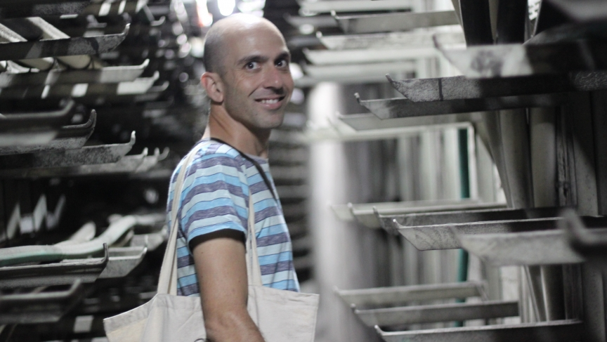 Yonatan Mishal, a photographer, leads independent tours of the Tel Aviv central bus station. Here, he's in a narrow tunnel inexplicably flanked by metal claws.
