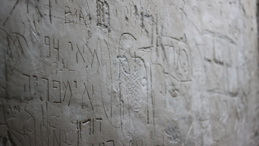 Names carved into a wall at the end of the metal claw tunnel.