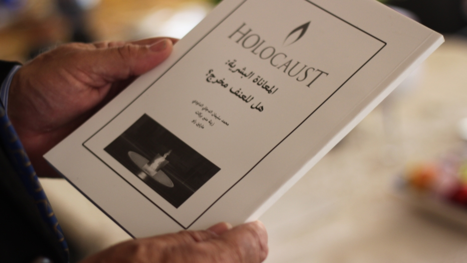 Palestinian professor Mohammed Dajani holding a booklet he recently authored on the Holocaust.