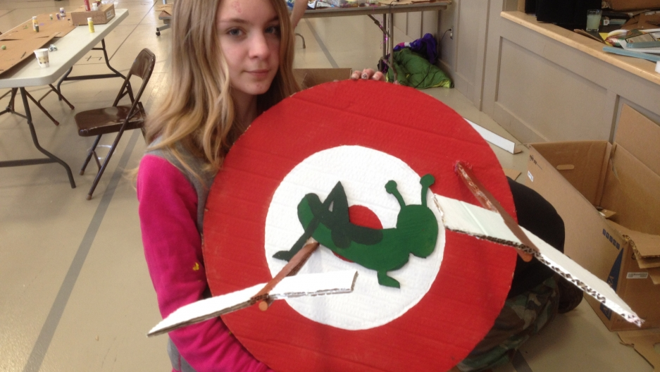 Aurora Ramsdell holds a target displaying a grasshopper pierced with arrows shot by St. Urho, the made-up Finish-American saint who freed Finland of grape-devouring grasshoppers. Finnish Americans in several towns in northern Minnesota and across the coun