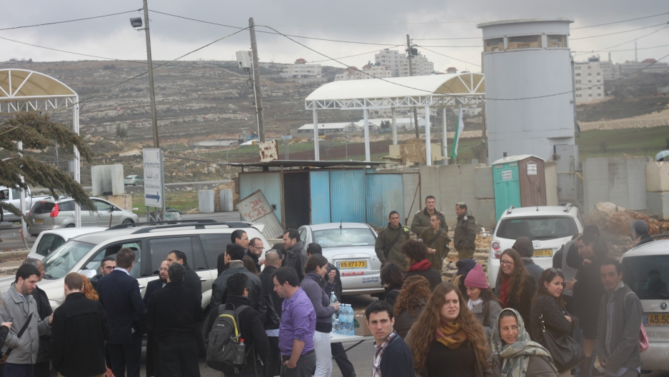 A group of Israelis gather near a checkpoint before boarding special buses to Ramallah. A Palestinian police car escorted the buses of Israelis through the streets of Ramallah.