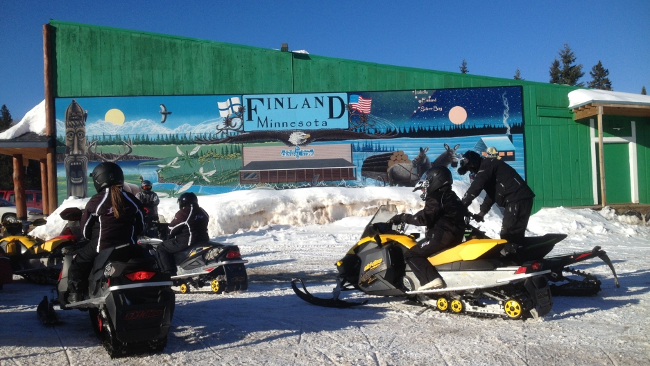 Snowmobilers take a break outside the general store in Finland, Minnesota a week before Saint Urho's Day.