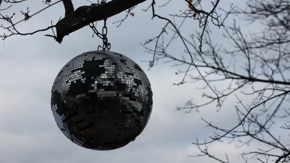 A disco ball hangs from a random tree in Berlin.