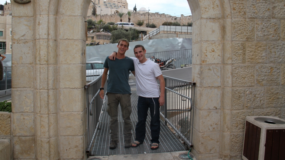 Young Jewish men posing at the entrance to the City of David archaeological park.