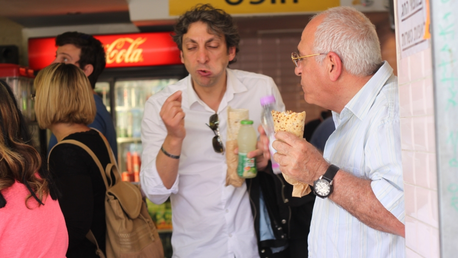 Customers eating shawarma sandwiches with kosher for Passover pita wraps made of soy and corn starch.