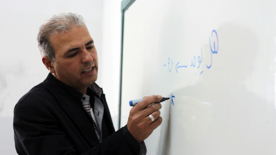 Esmat Mansour writing in Hebrew and Arabic on the whiteboard.