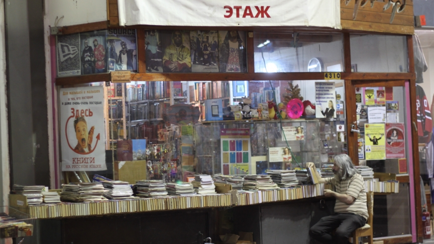 A bookseller at a Russian language bookshop in the bus station.