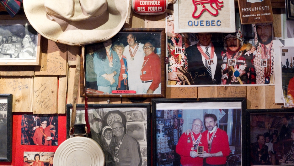 An old-style caribou flask hangs on the wall with historic photos at the Voûte à 'Ti-Père.