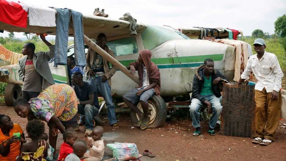 Young men with machetes and knives saying they are providing security, join Christians gathered in a makeshift camp for internally displaced people set up in the airport in Bangui, Central African Republic.