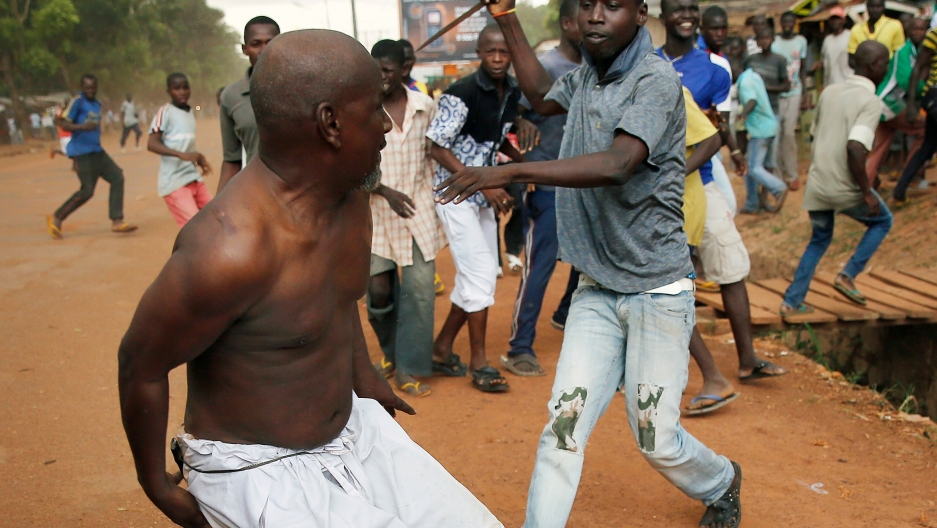 A Christian man chases a suspected Seleka officer in civilian clothes with a knife near the airport in Bangui, Central African Republic.