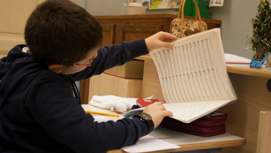 A student flips through his music exercise book. Each class spends at least 2 hours a day on music theory.