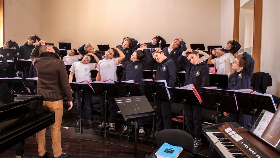 Music teacher Adriano Caroletti leads stretching exercises before a rehearsal.
