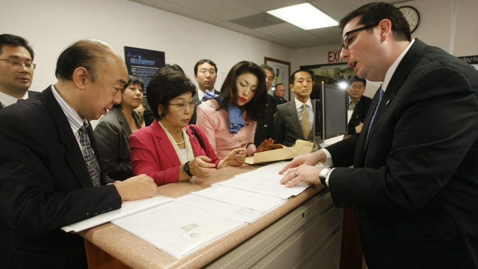 "Tokyo councilwoman Yoshiko Matsuura presents Glendale, California, city clerk Ardashes Kassakhian with a letter demanding the city remove its memorial to World War Two-era ""comfort women."""