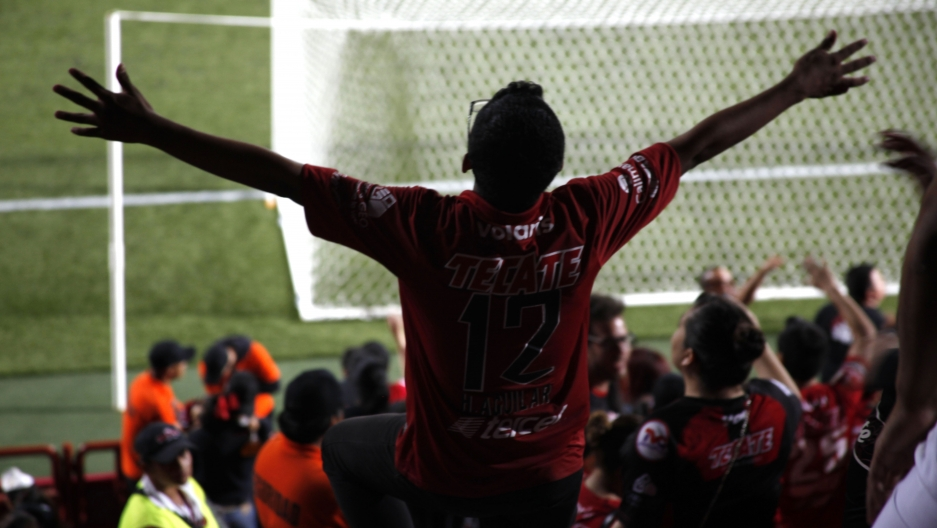 A fan cheers during a Xolos match. Soccer writer Jonny Aviles says the Tijuana team aggressively recruited from the US. As the team's success grew, other Mexican teams also began looking for talent across the border.