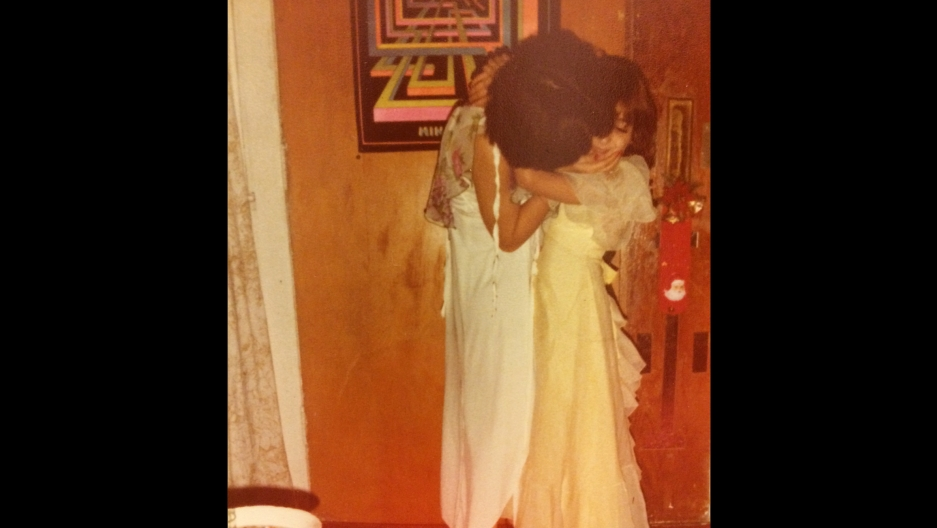 Eight-year-old Susan Cruz and her mother in 1978. Cruz is wearing a treasured yellow dress, one of the few items she brought from El Salvador.