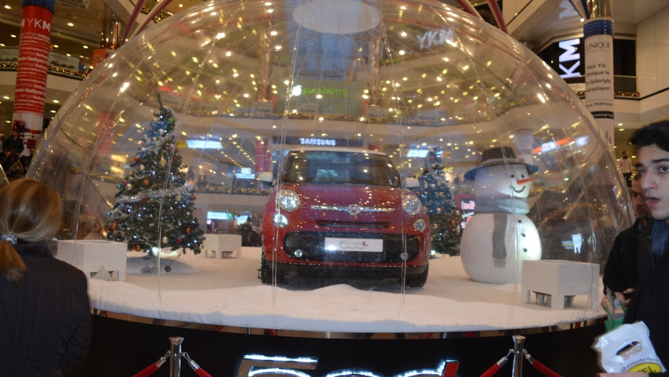 A giant snow globe featuring a tree, Frosty and a mini-cooper giveaway car stand at the mall's entrance.