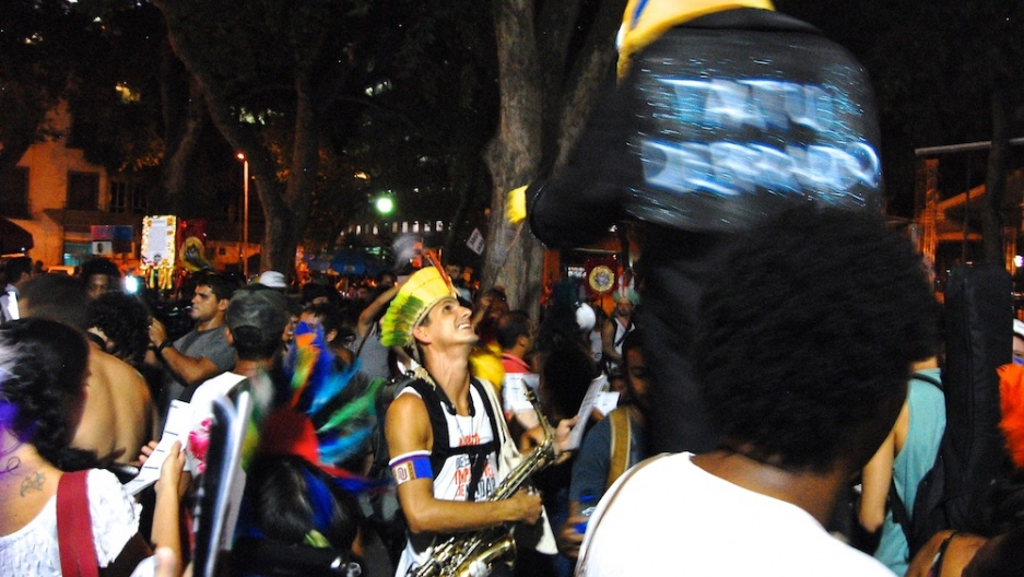 Occupy Carnival organizer Tomás Ramos speaks with a spoof of the FIFA 2014 World Cup mascot.