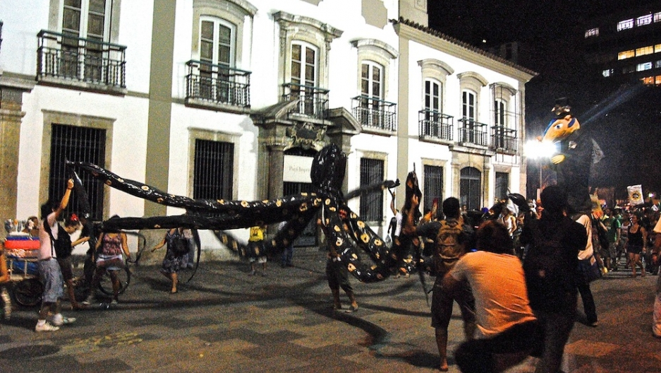 """A giant octopus (in Portuguese """"polvo"""") leads an anti-Cabral carnival party for the people (in Portuguese """"povo"""")."""
