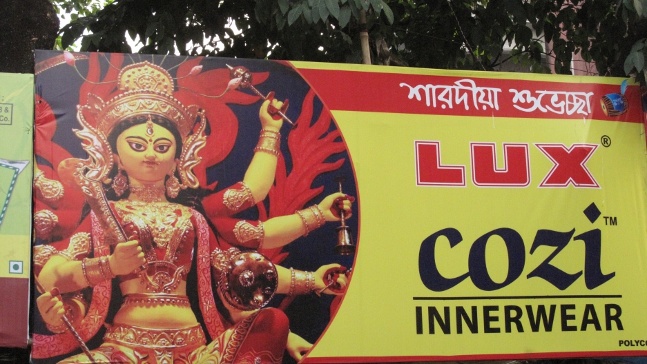 The festival has become increasingly commercialized, with businesses advertising products in the name of Durga. This one shows an underwear ad with Durga's face on the banner.
