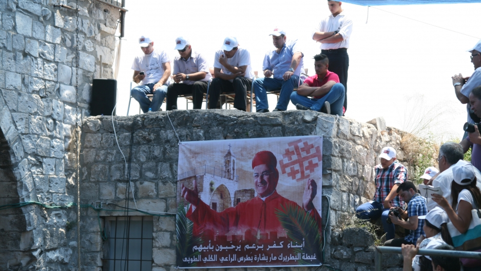 Cardinal Bechara Rai's visit to the ruins of the Maronite village Kfar Biram was historic, and locals greeted him beneath massive posters, wearing baseball caps emblazoned with his picture.