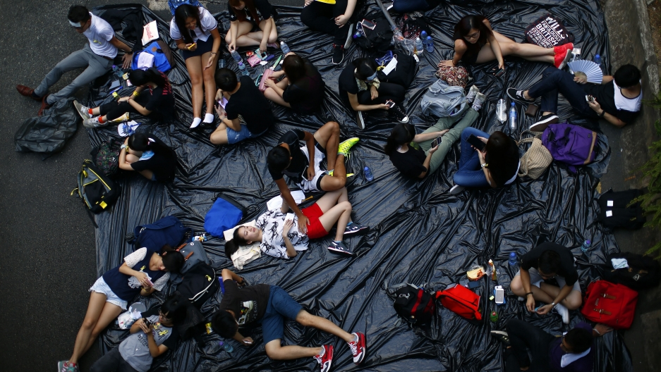 Protesters lie on tarpaulin as they block a street near the government headquarters building in Hong Kong on September 30, 2014.