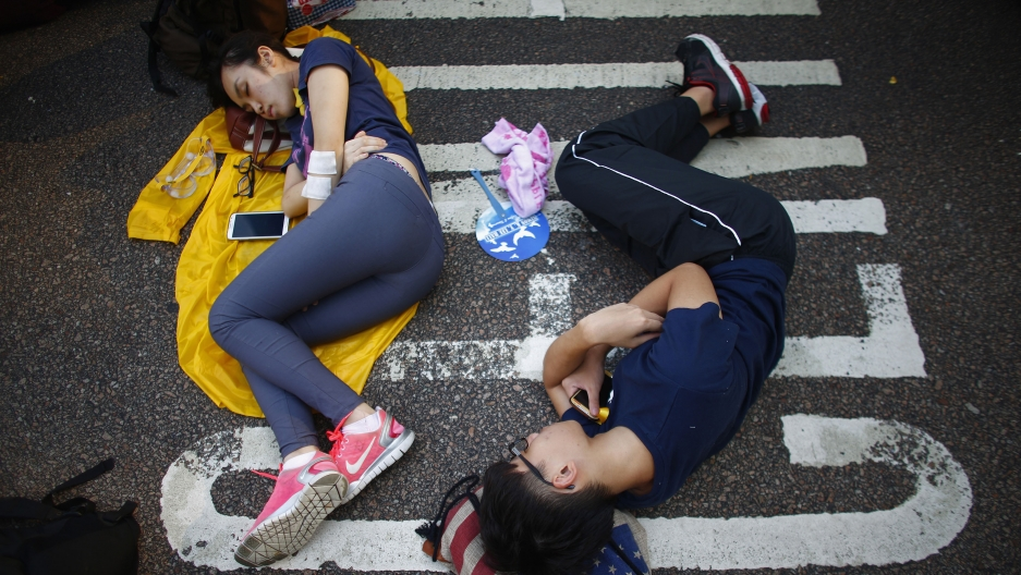Protesters sleep as they block a street outside the government headquarters in Hong Kong September 30, 2014.