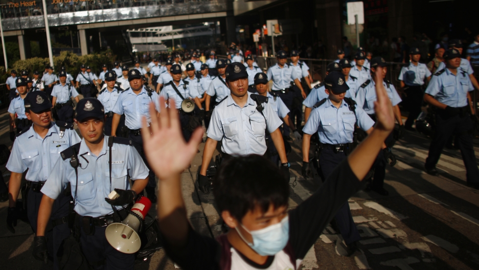 A protester raises his arms as police officers try to disperse the crowd near the government headquarters in Hong Kong on September 29, 2014.