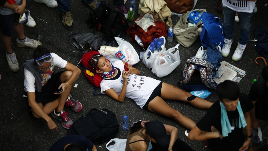 A protester lies on the street as she joins others in blocking the main street to the financial district in front of the government headquarters in Hong Kong on September 29, 2014.