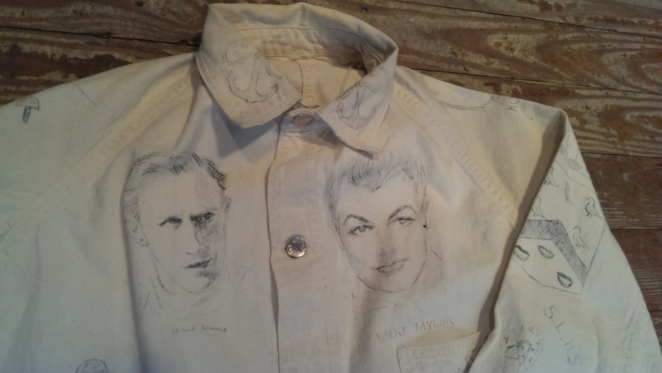 "A white, canvas button-down workwear jacket that has been ""tattooed"" with handmade ink drawings. Found in the Adirondacks and probably dates from the 1940s."