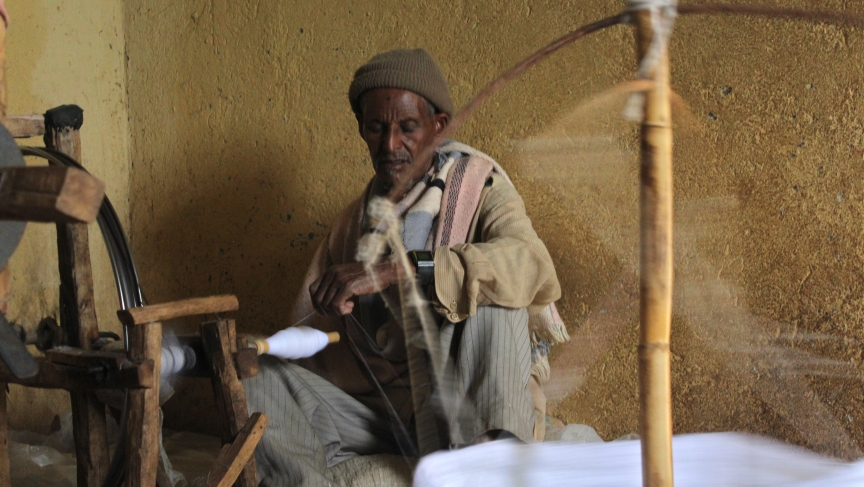 A man doing what is traditionally considered women's work: spinning.