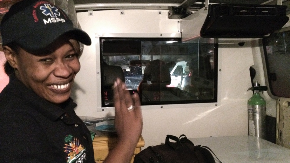 Beatrice, an ambulance paramedic, sits in the back of her ambulance in Port-au-Prince, Haiti.