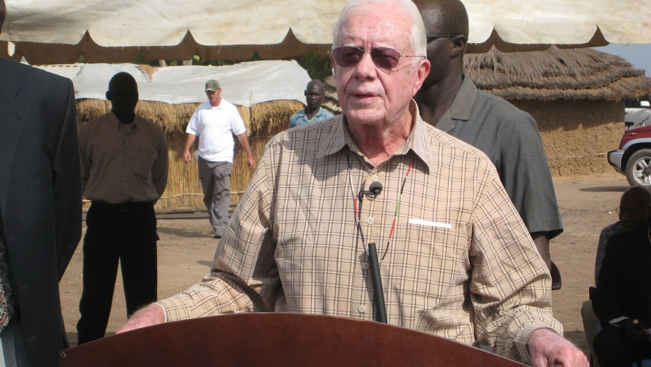 Former US President Jimmy Carter in Lojora Village. A pipe filter, of the sort locals use to protect against Guinea worm, hangs from his neck.