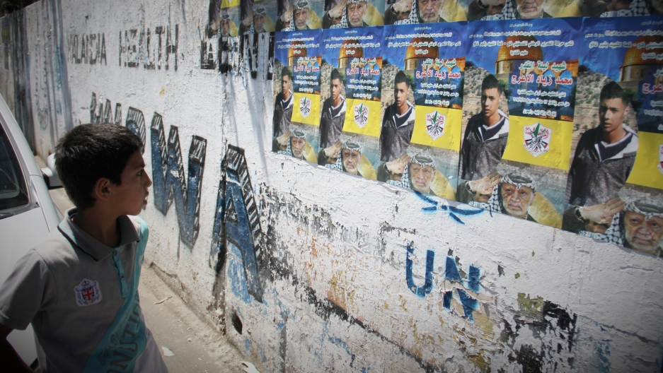 A boy in the Qalandiya refugee camp looks at a martyr poster of Mohammed Al-Araj, who was killed in clashes with the Israeli army.