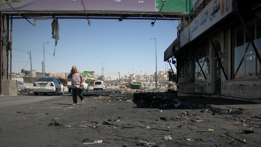 A man walks through the charred Qalandiya checkpoint after clashes between protesters and the Israeli army.