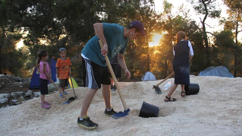 Settlers shovel gravel at the site.