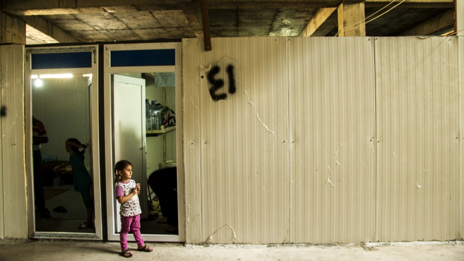 A young girl from a village outside Mosul, stands beside a prefab room where her family lives inside a half finished mall in the Northern Iraqi city of Erbil.
