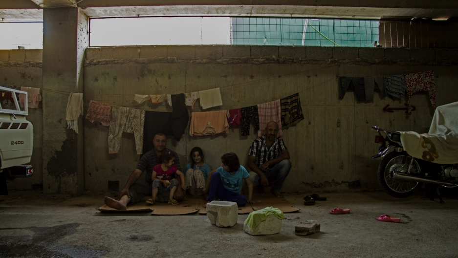 A family sits on flattened cardboard boxes in the underground parking lot of an unfinished mall in Erbil.