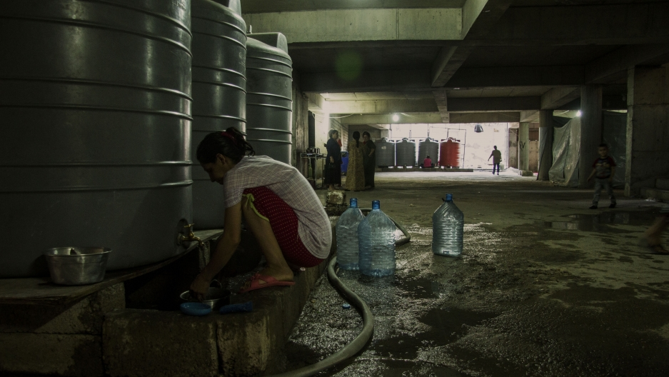 A young woman washes dishes beside a water tank in the basement of the half finished in Erbil where she and her family now live. They moved here after being driven from their village outside Mosul by violence.
