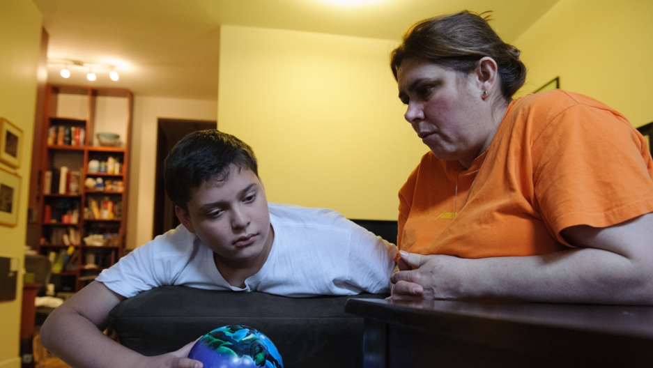 Blanca sits with her son, Guido, in the house where she works as a nanny. The two-year-old child she cares for is same age Guido was when she left him with her mother in Paraguay a decade ago.