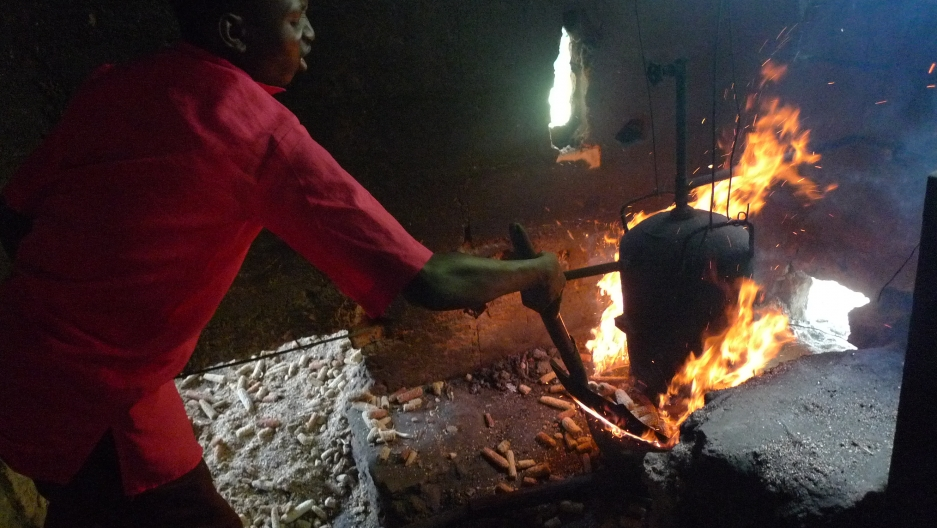 A worker feeds corn cobs—collected from local farms—into the furnace, as fuel.