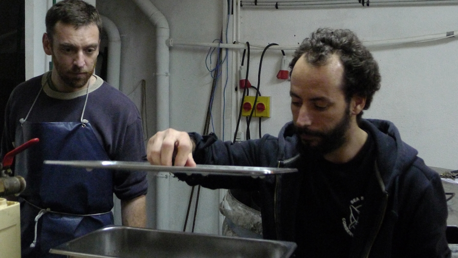 """Salem and his business partner, Sylvain, inspect their latest batch of microbrew in the lab section of Biere de la Plaine. They're unique recipes have earned the moniker """"brewing bad,"""" a play on the TV series """"Breaking Bad""""."""