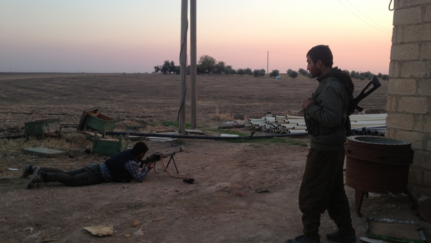 Two Kurdish fighters guard a tiny farm. It's the most forward outpost of the YPG. Al-Qaeda-linked brigades are holed up in buildings just a few football fields away.